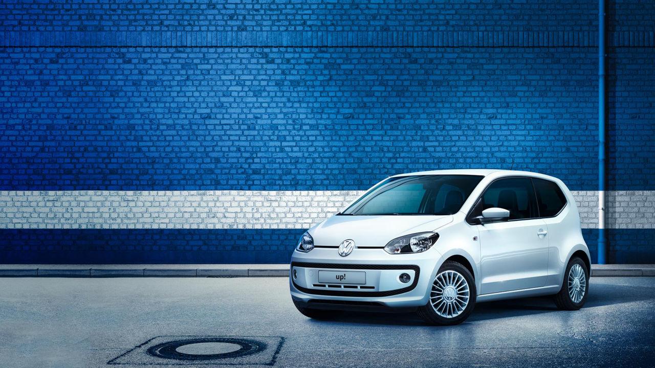 Vista 3/4 frontale di Volkswagen up! parcheggiata fuori da un edificio con le pareti blu.