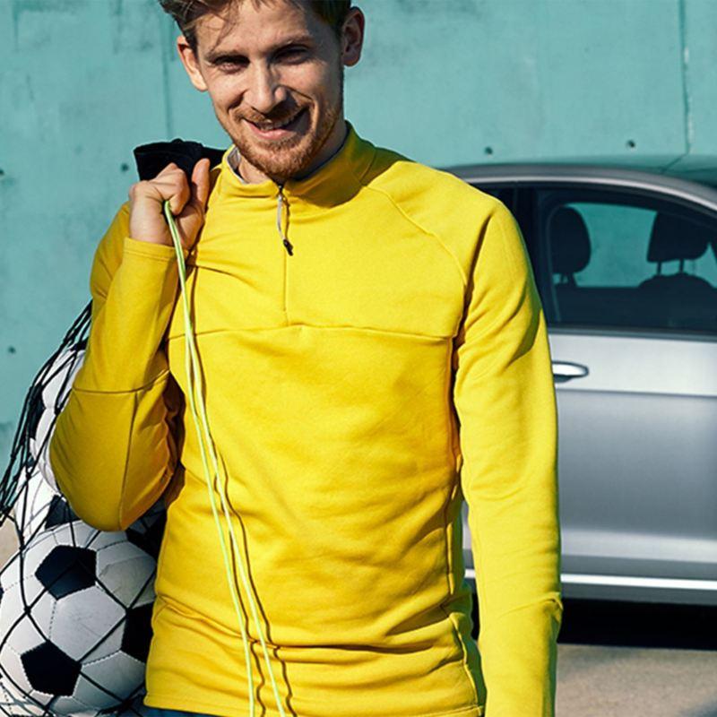 Un homme jouant au soccer avec un chandail jaune