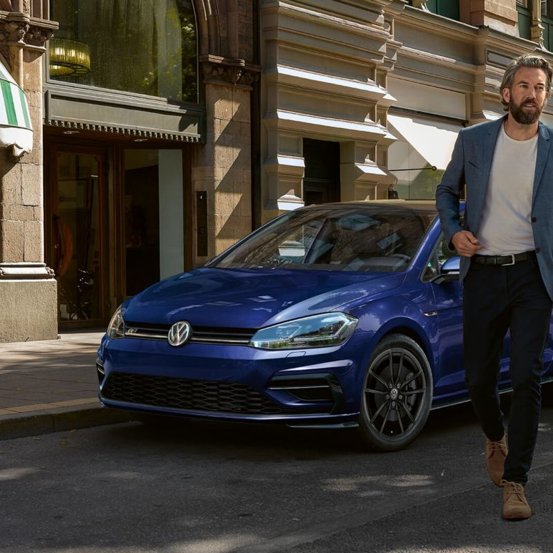 Un homme laissant sa Volkswagen pour aller faire des emplettes, lien vers la page «  véhicules certifiés » de VW