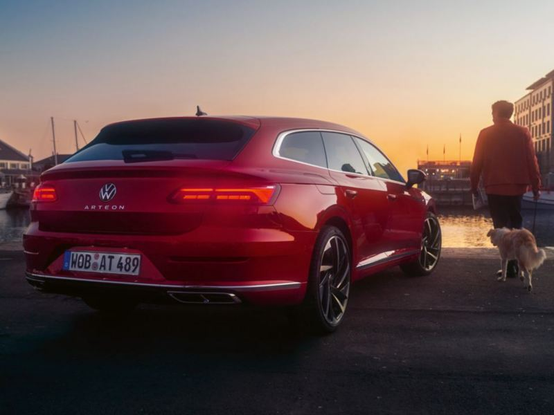 A tail light view of a red Arteon Shooting Brake parked at a dock, with a man and dog walking alongside it.