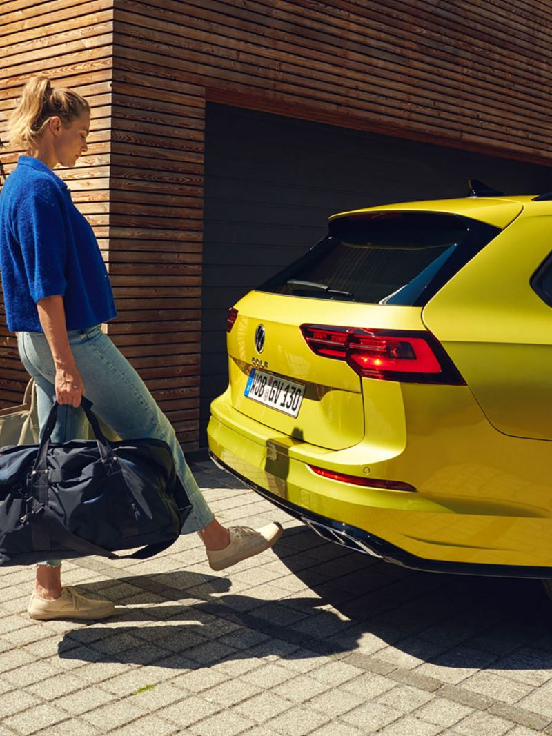 A woman holding luggae waving her foot under the vehicle so that the boot lid opens.