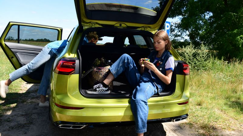 A girl sat in the open boot of a yellow Golf Estate 8, playing with a rubix cube.