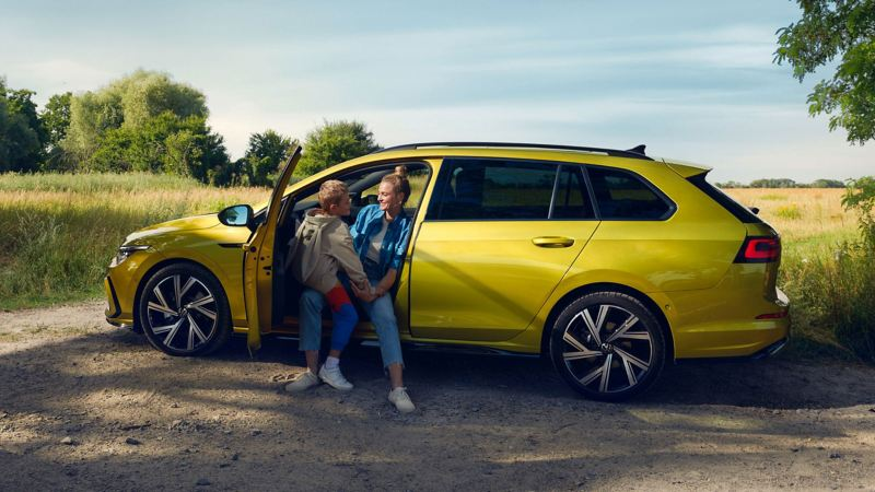 A woman and son sat in a parked yellow Golf Estate 8 in a field.