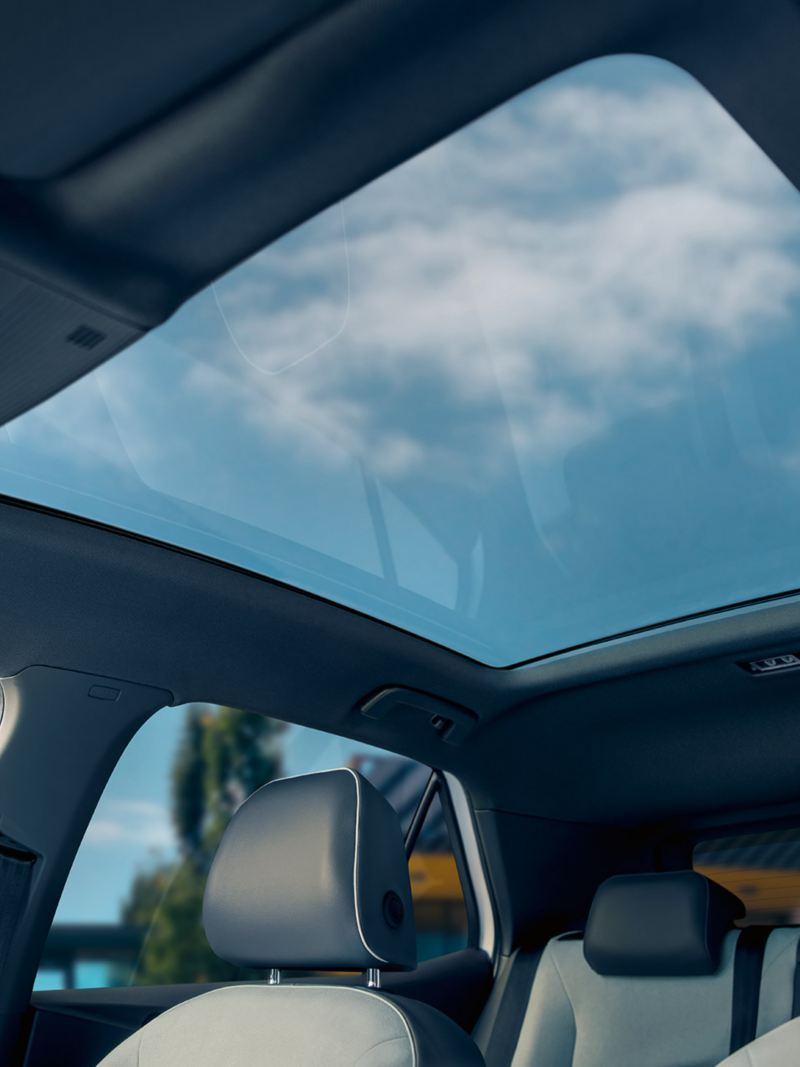A view of a cloudy blue sky through the ID.3 panoramic sunroof.