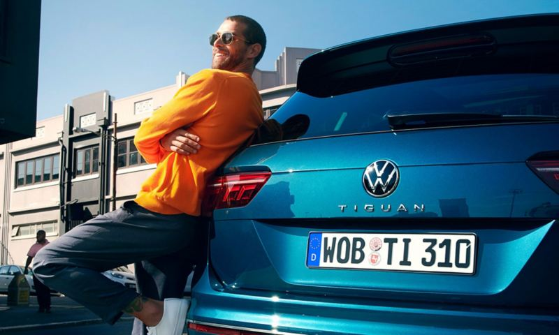 A man leaning against the boot of a Blue New Tiguan.