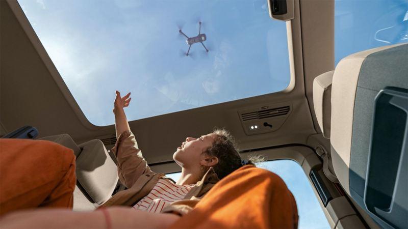 Une petite fille tend la main vers le toit vitré panoramique et regarde un drone qui plane au-dessus de la voiture.