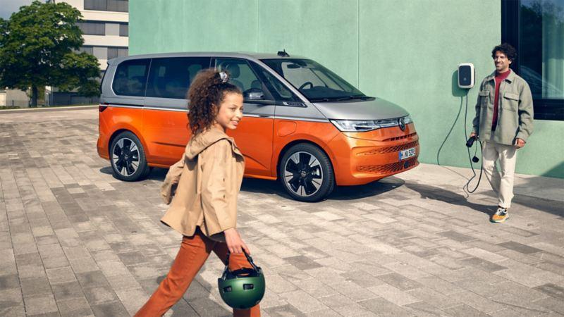 Un homme avec un câble de recharge en main et une petite fille avec un casque devant un Multivan Energetic.
