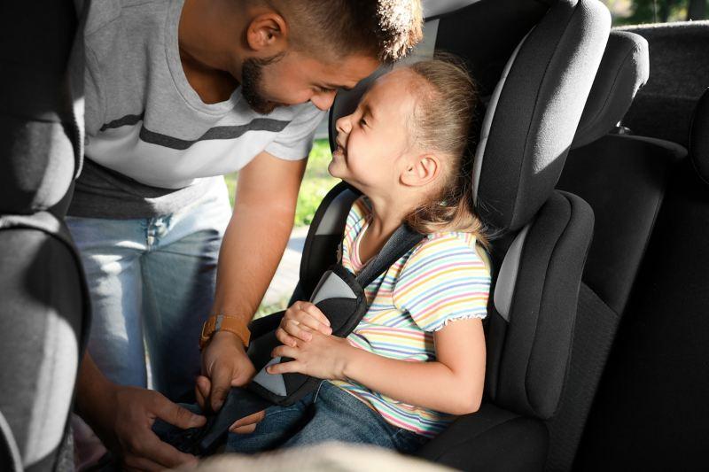 Ein Vater schnallt seine Tochter im Kindersitz im Auto an.