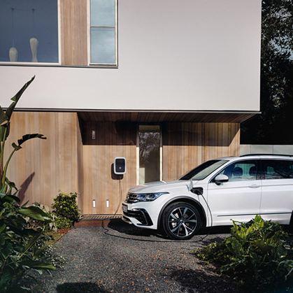 Ein weißer VW Tiguan eHybrid lädt an einer ID. Charger Wallbox.