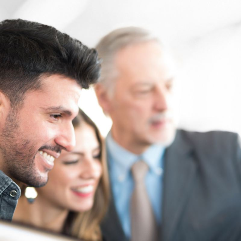 Ein junges Paar lässt sich von einem Volkswagen Partner zu den VW Elektroautos beraten.