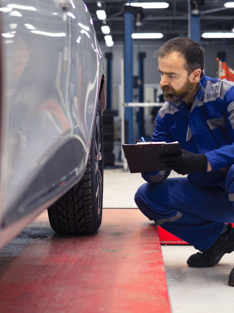 Ein Service-Techniker von VW inspiziert die Reifen eines Elektroautos.