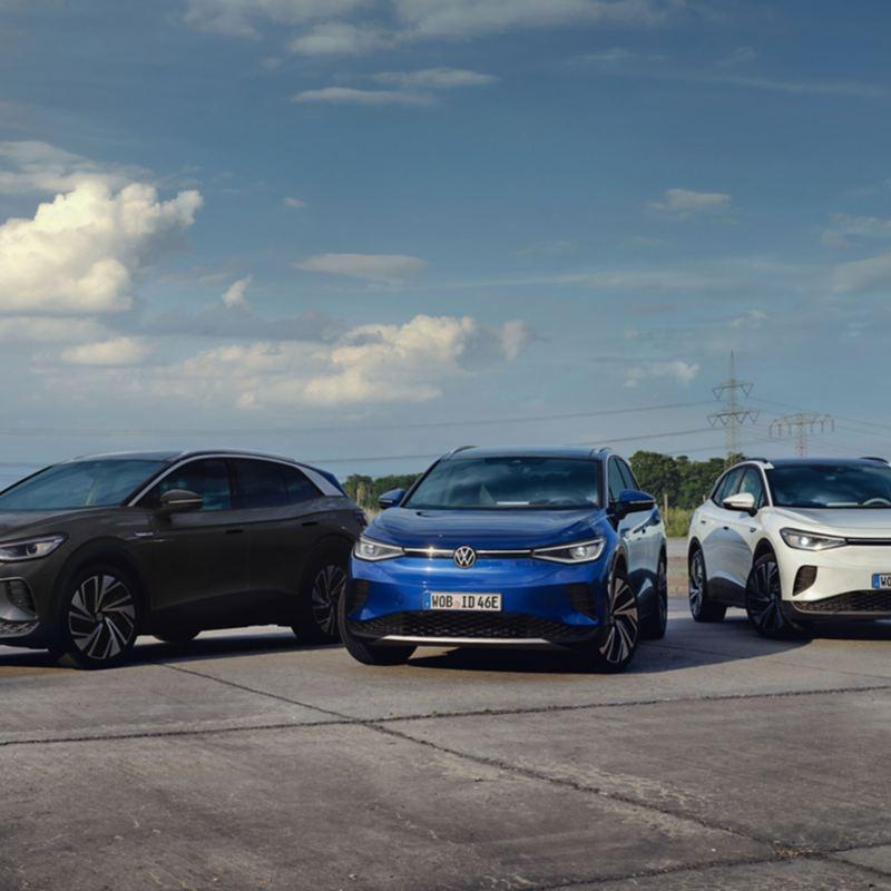 Drei verschiedene Modelle des VW ID.4 in Schwarz, Blau und Weiß stehen auf einem Asphaltplatz.