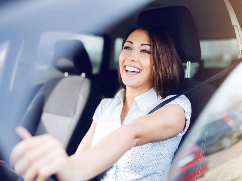 Eine junge Frau sitzt am Steuer eines VW Elektroautos und strahlt.