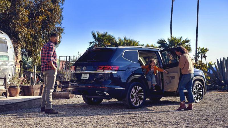 Niña bajando de la innovadora camioneta Teramont azul en compañía de sus padres.