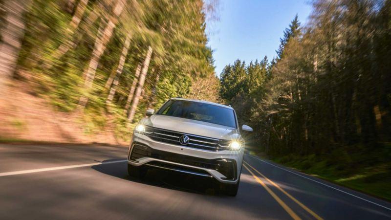 Nueva camioneta familiar Tiguan VW en carretera rodeada de bosque