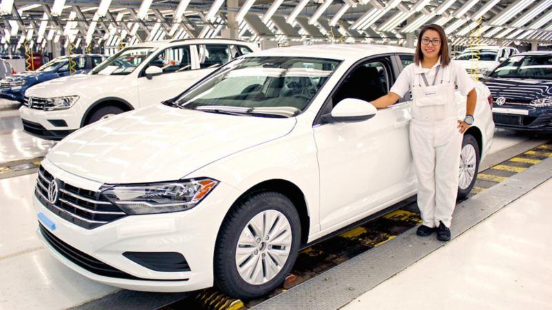 Mujer trabajadora con Jetta blanco en planta VW