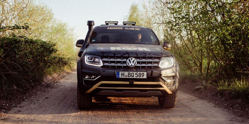 Ein VW Amarok von vorne fährt auf einem Grantweg,