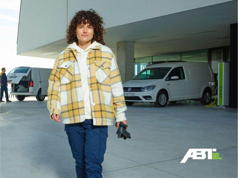 Vivien Peters steht med en VW ABT e-Caddy.