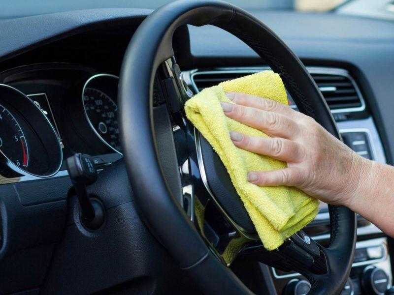 Imagen de muestra a una mujer limpiando el volante de su auto Volkswagen.