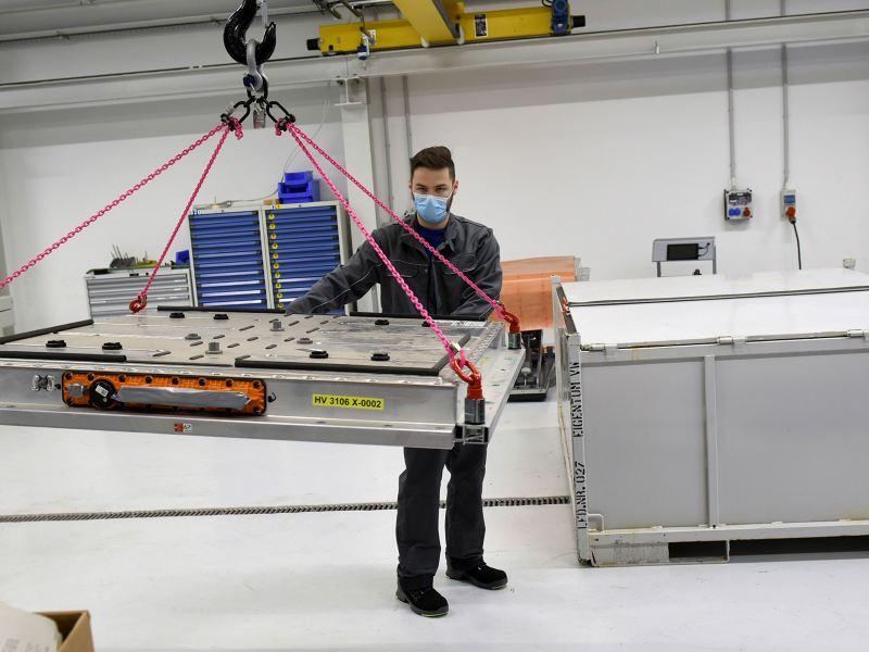 Ein Volkswagen Mitarbeiter recyclet die Batterie eines Elektroautos