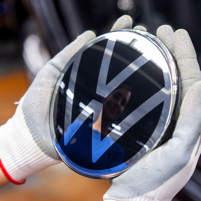 Una donna tiene fra le mani il logo Volkswagen