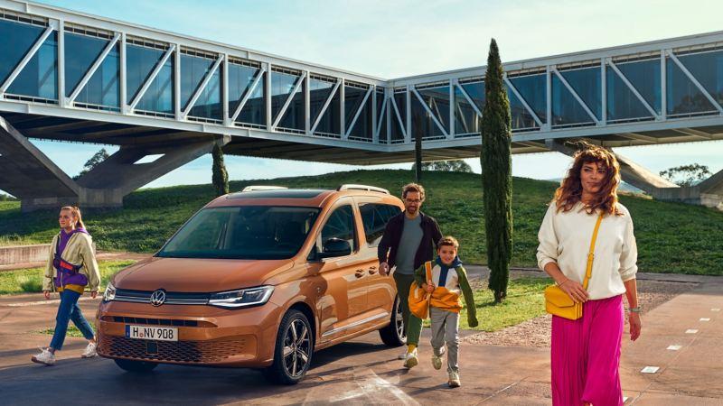 Una famiglia scende da un Nuovo Caddy Volkswagen, visto 3/4 frontalmente e fermo in un parcheggio.