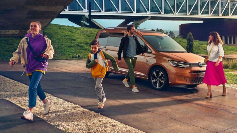 Una famiglia si allontana dal suo Nuovo Caddy Volkswagen, visto lateralmente.