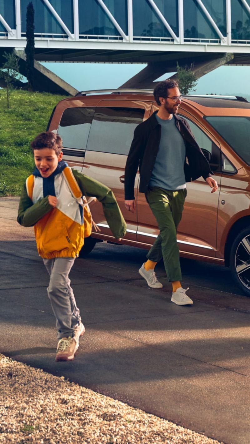 Familj framför en Volkswagen Caddy personbil