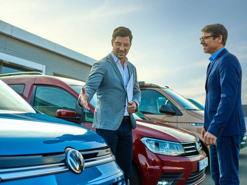 Ein Mann zeigt einem Kunden ein Gebrauchtwagenfahrzeug von Volkswagen Nutzfahrzeuge.