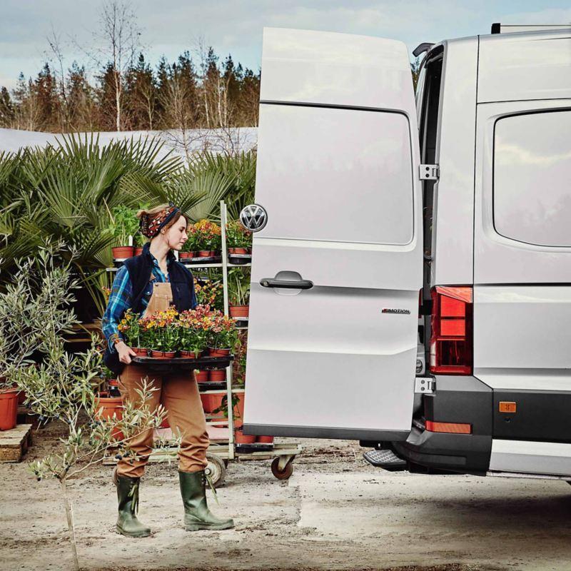 Kvinnlig trädgårdsmästare lastar en VW Crafter lätt lastbil