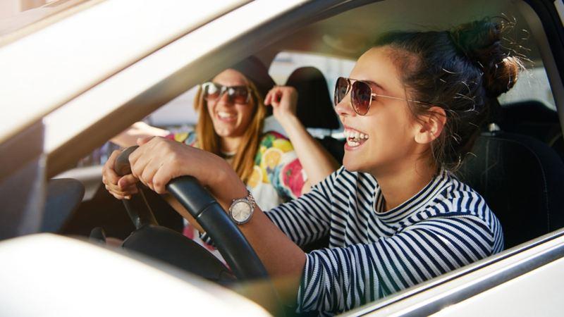 zwei Frauen sitzen im Auto und lachen