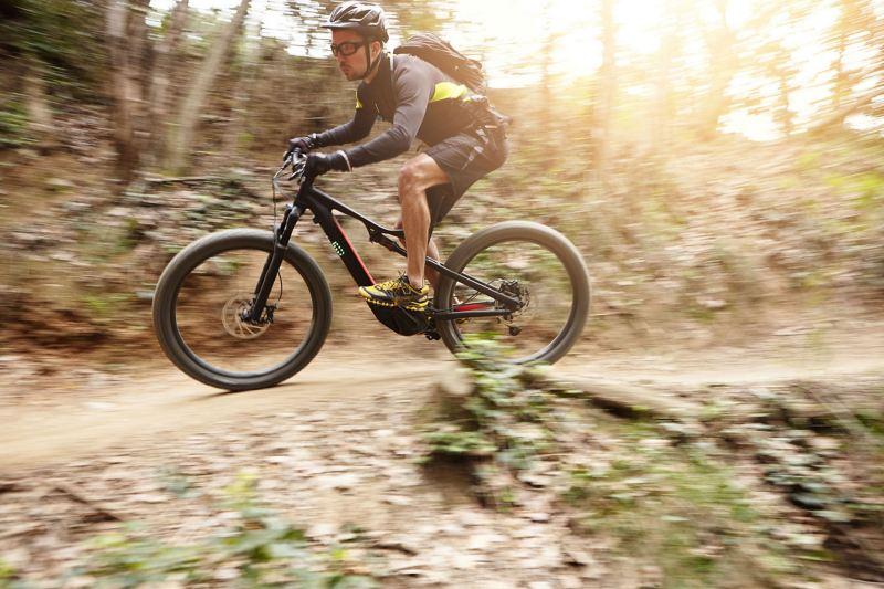 Ein Mountainbiker auf einem E-Fully fährt über einen schmalen Waldweg.