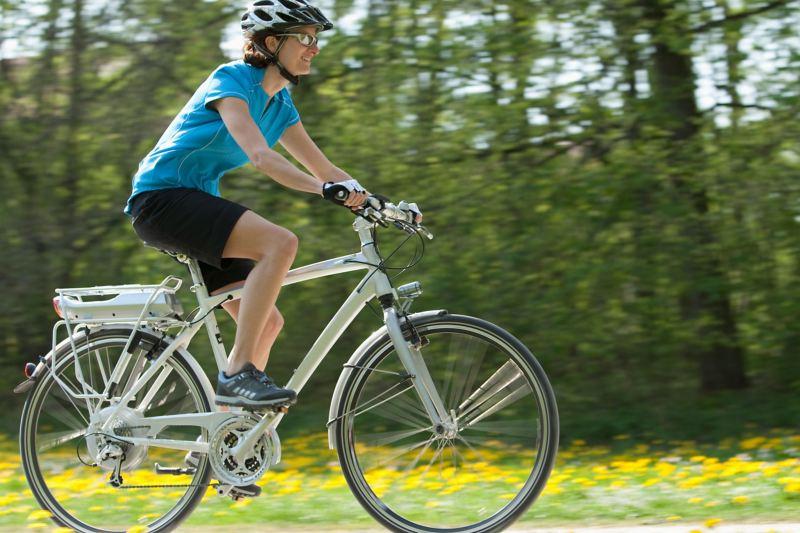 Eine Radfahrerin rollt auf einem silbernen Trekking-E-Bike über einen Feldweg