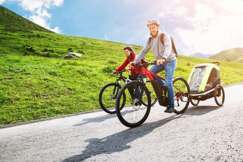 Eine Familie ist mit E-Bikes in der Natur unterwegs, das Kind wird in einem Fahrradanhänger transportiert