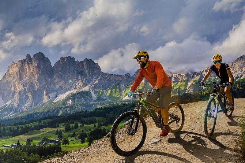 : Zwei Radsportler auf E-Mountainbikes fahren durch eine spektakuläre Bergkulisse.