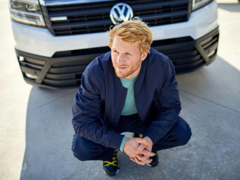 Bildet viser en håndverker som sitter på huk foran en hvit Volkswagen e-Crafter elvarebil