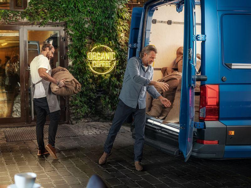 Barman i dostawca wyładowujący worki z kawą z e-Craftera
