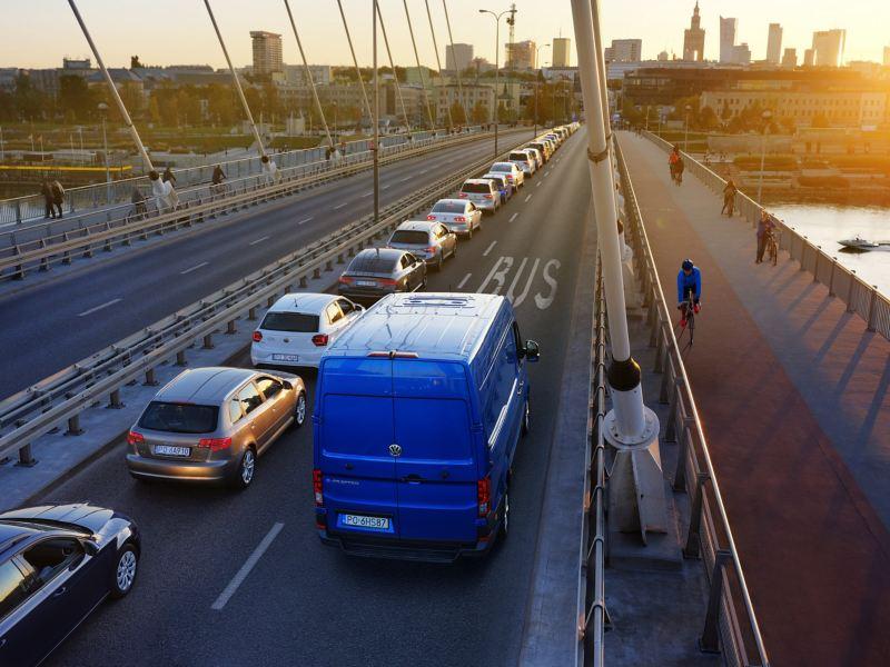 Niebieski Volkswagen e-Crafter z wysokim dachem przejeżdża most buspasem.