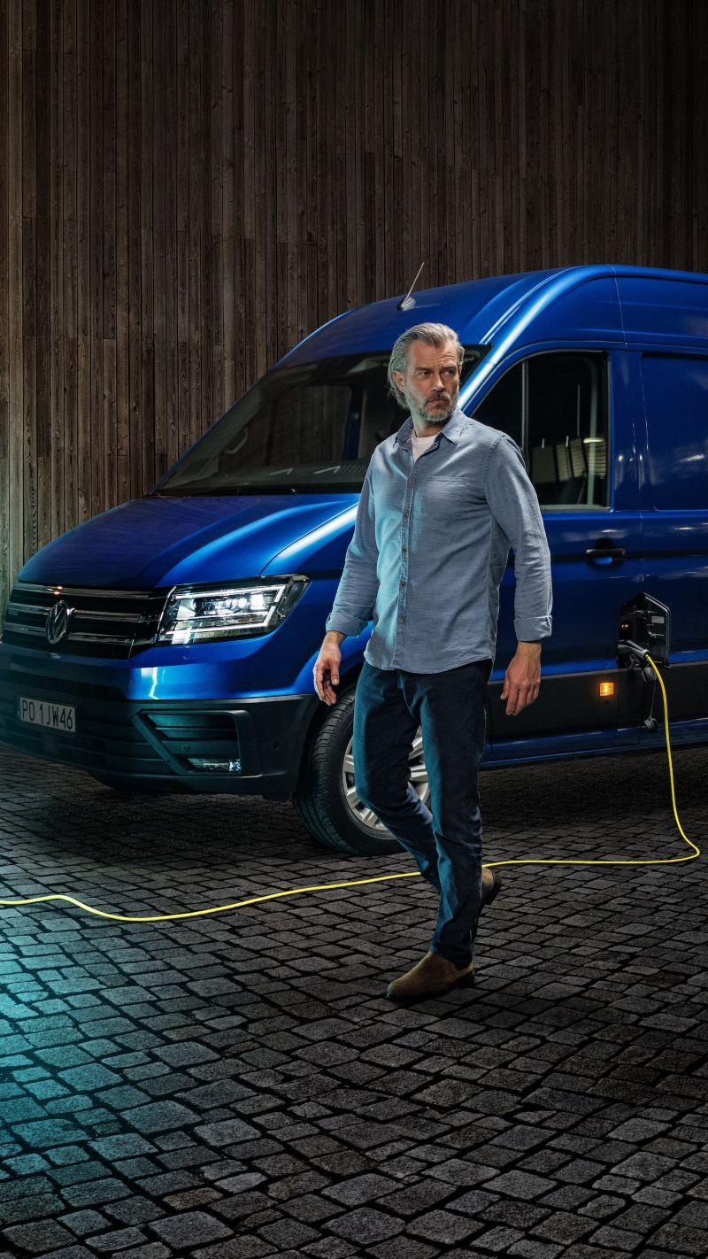 Niebieski Volkswagen e-Crafter z wysokim dachem podczas ładowania.
