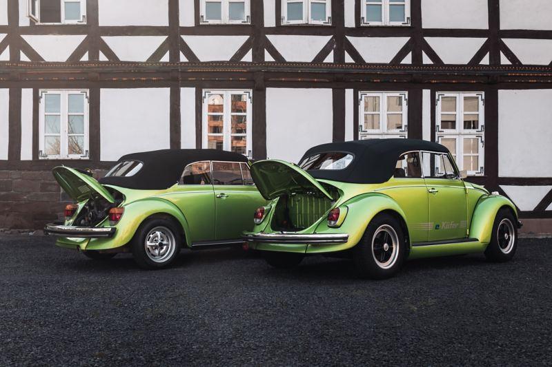Zwei Volkswagen Käfer Cabrios mit geöffneter Heckklappe, einmal mit Boxermotor, einmal mit Kofferraum.