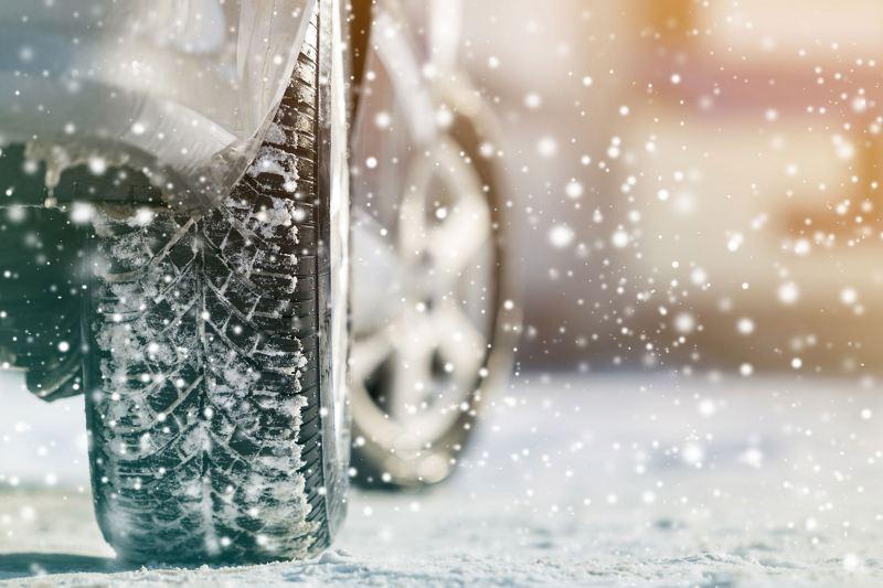 Ein Autoreifen auf verschneiter Fahrbahn
