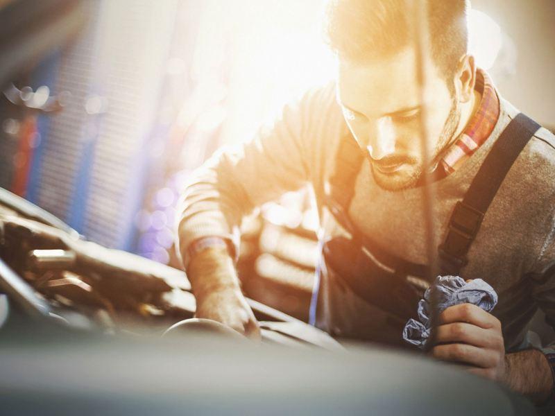 Ein Kfz-Mechatroniker inspiziert ein Fahrzeug