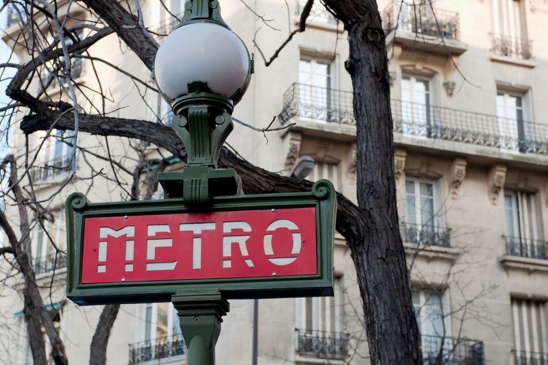 Ein rotes Straßenschild weist eine Metrostation in Paris aus.