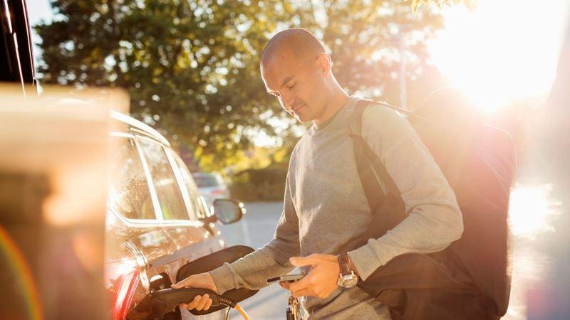 Ein Mann mit Einkaufstaschen auf dem Weg zu seinem Elektroauto, das gerade aufgeladen wird.