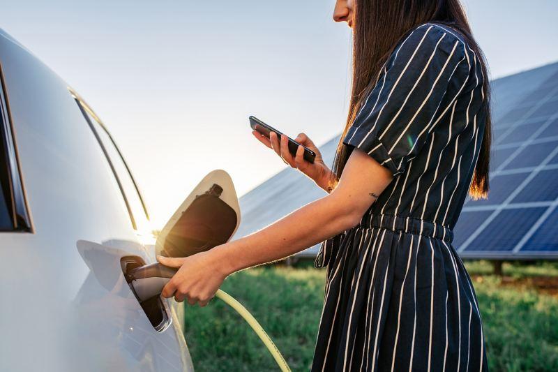 Eine junge Frau schließt ein Ladekabel an ihr Elektroauto an, im Hintergrund eine Solaranlage.