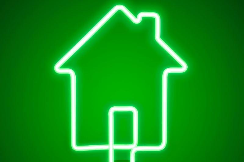 Eine grün leuchtende Neonlampe in Form eines Hauses.