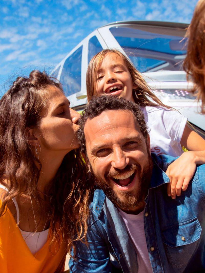 Familia en playa, de fondo Volkswagen ID. Buzz