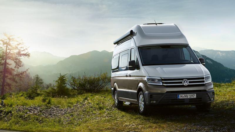 Der VW Grand California steht vor einem Bergpanorama.