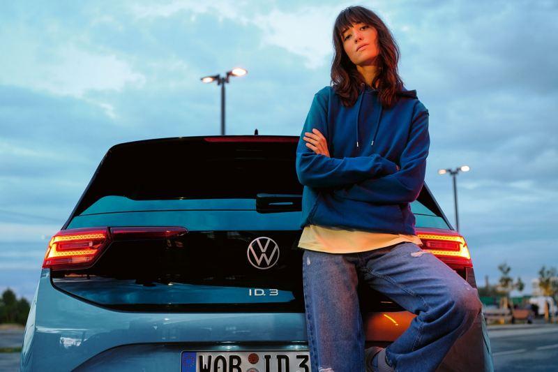 Eine Frau lehnt mit dem Rücken am Kofferraum eines VW ID.3