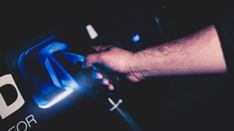 Es ist dunkel, eine Männerhand hält ein Ladekabel in der Hand und lädt ein E-Auto.